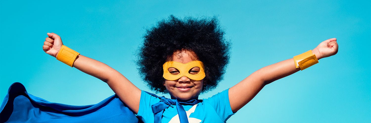 kid with arms outstretched and super-hero cap and mask on blue background for the BRAVE Research Center (formerly known as BRAVE Youth Lab)